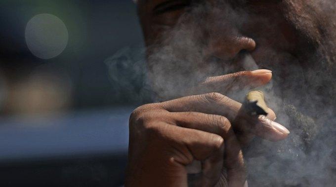 Мужчина курит марихуану в парке Civic Center, Денвер, сентябрь 2013. Изображение № 1.