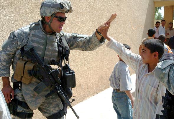 Солдат американской армии отбивает пять иракскому школьнику, 2008 год. Изображение № 6.