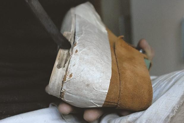 На рант подошвы я наношу слой пчелиного воска, после чего вжариваю нагретым до нужной температуры токмачом (специальный инструмент для полировки каблука и боковой поверхности подошвы). Изображение № 48.