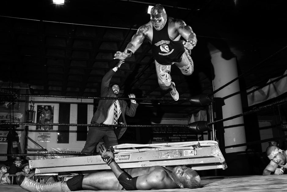 Dainja, a villainous character, lies  under a stack of ladders and a folding chairs while Bronco Internacional flies off the ropes to belly flop squarely onto the pile of metal and flesh.. Image 11.