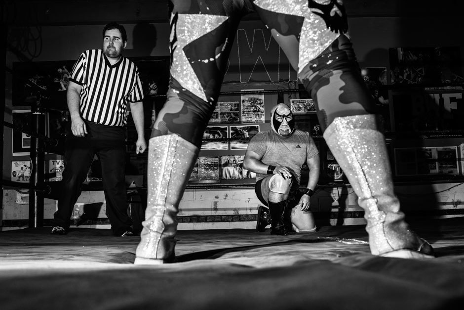 Barbaro stares down his opponent, Astro Negro during a match on November 7th. Generally, the bright neon colors and wide, froggy features of traditional luchador masks reference the iconography of Aztec history, evoking animals and gods.. Image 20.