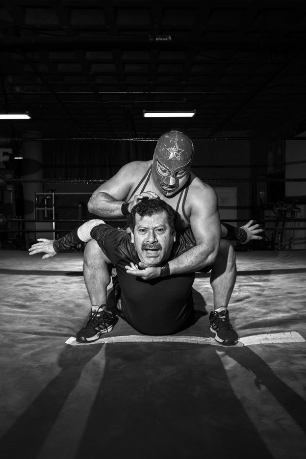 "El Pequeno Pierrot (The Little Harlequin) puts his opponent in a headlock during practice. ""You have to sell it,"" said Batsu, the Rad Dragon, of performing pain. ""At the show, if a guy's not making enough noise, the guy who's attacking will make him feel some real pain so he gets louder."" . Image 9."