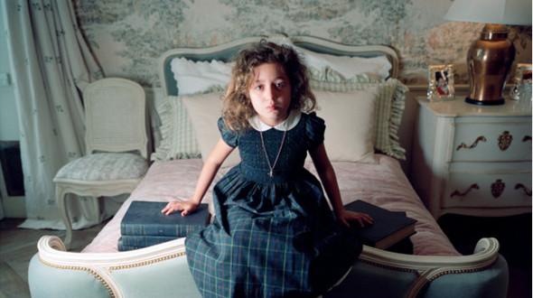 """""""Этия у себя в спальне"""", Москва 2009.  Во время нашей фотосессии Этия вела себя застенчиво и не могла решить, что ей надеть. Наконец-то она выбрала платье """"французской школьницы"""", которое хорошо сочеталось с убранством ее спальни и энциклопедическими словарями, лежащими на кровати. Но облупленный красный лак на ногтях и маленькая подвеска в виде скелета намекают на то, что где-то под хорошими манерами и пристойным окружением прячется ее мятежная натура.. Изображение № 9."""
