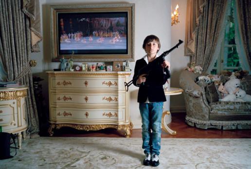 """""""Яков стреляет по балеринам"""", Москва 2009.  Изначальный план был поснимать сестру Якова, но в свои 13 лет она уже казалась чересчур взрослой для этого проекта. Когда я зашла в комнату Якова, он сидел на кровати. А рядом с ним лежала коллекция оружия, в основном Калашниковы, настоящие. Он взял старый пистолет, который в свое время служил нацистам в Великую Отечественную войну, и стал притворяться, будто стреляет по балеринам, кружащимся по экрану телевизора. Перед моим визитом его бабушка заходила к нему в комнату включить культурный канал, наверное, чтобы сбалансировать коллекцию оружия.. Изображение № 3."""
