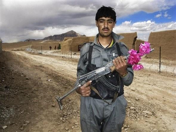Guns & Roses.  Один из участников шествия вокруг Аскота. Даже во время пути в отверстие АК47 вставлен цветок.. Изображение № 4.