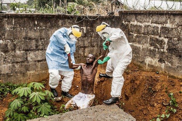 Сотрудники медицинского центра в Сьерра-Леоне возвращают в изолятор больного Эболой мужчину, который в бреду пытался оттуда сбежать / Автор: Pete Muller. Изображение № 13.