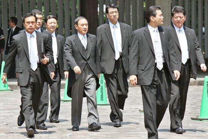 Генеральный секретарь кабинета министров Японии Йошихиде Суга (по центру). Изображение № 1.