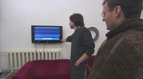 Деятель современного искусства объясняет Розенталю, что для русских важнее не содержание, а обертка, и в качестве примера приводит свою работу — телевизор, который показывает деконструированный концерт Бритни Спирс. Изображение № 3.