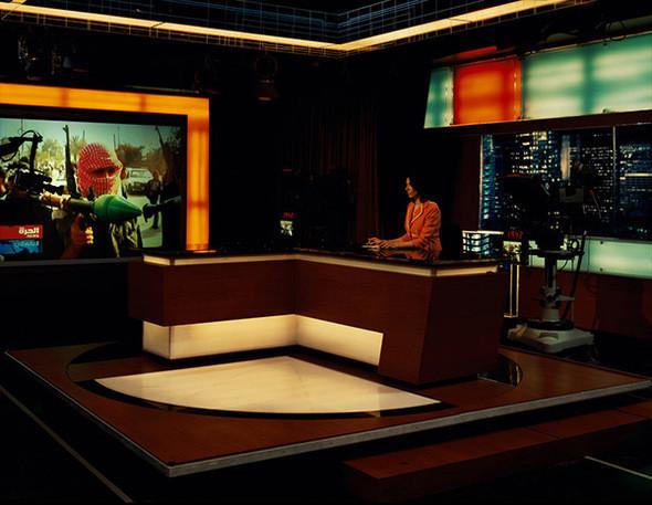 Телевидение Alhurra. Аппаратно-студийный блок (Спрингфилд, Вирджиния). Anchor Mona Atari за столом новостей Alhurra. Спонсируемый правительством арабский языковой телевизионный канал передает прежде всего новости. В феврале 2004 г. было утановлено 24-часовое вещание без рекламы, рассчитанное на еженедельную аудиторию в 21 млн. в 22 арабских странах. В апреле того же года канал был запущен. Ст. 501 U.S. Information и Education Exchange Act, принятая Конгрессом в 1948 г., уполномочивает американское правительство распространять информацию о политике США за границей. В то же время ст. 501 запрещает внутреннее распространение той же самой информации, поэтому внутри США вещание канала Alhurra является запретным. . Изображение № 13.