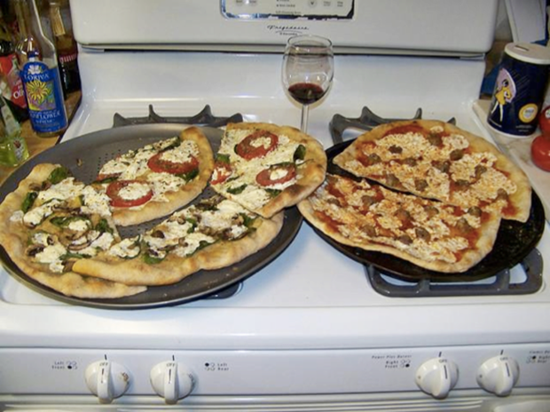 """Two pizzas sitting on top of a stove top oven"" («Две пиццы на плите»). Изображение № 1."