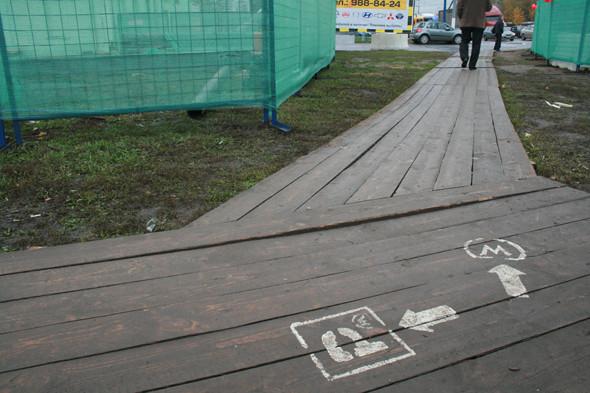 От метро к парковке ведет деревянный настил, правда, белые знаки быстро стираются в ноябрьской слякоти.. Изображение № 5.