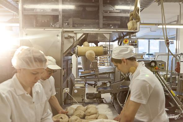 Тесто попадает на стол, где пекари формируют каждый кусок в кольцо. Изображение № 16.