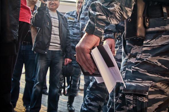 Один из полицейских прохаживается со стопкой паспортов, сотрудник в штатском снимает всех задержанных на видеокамеру.. Изображение № 11.