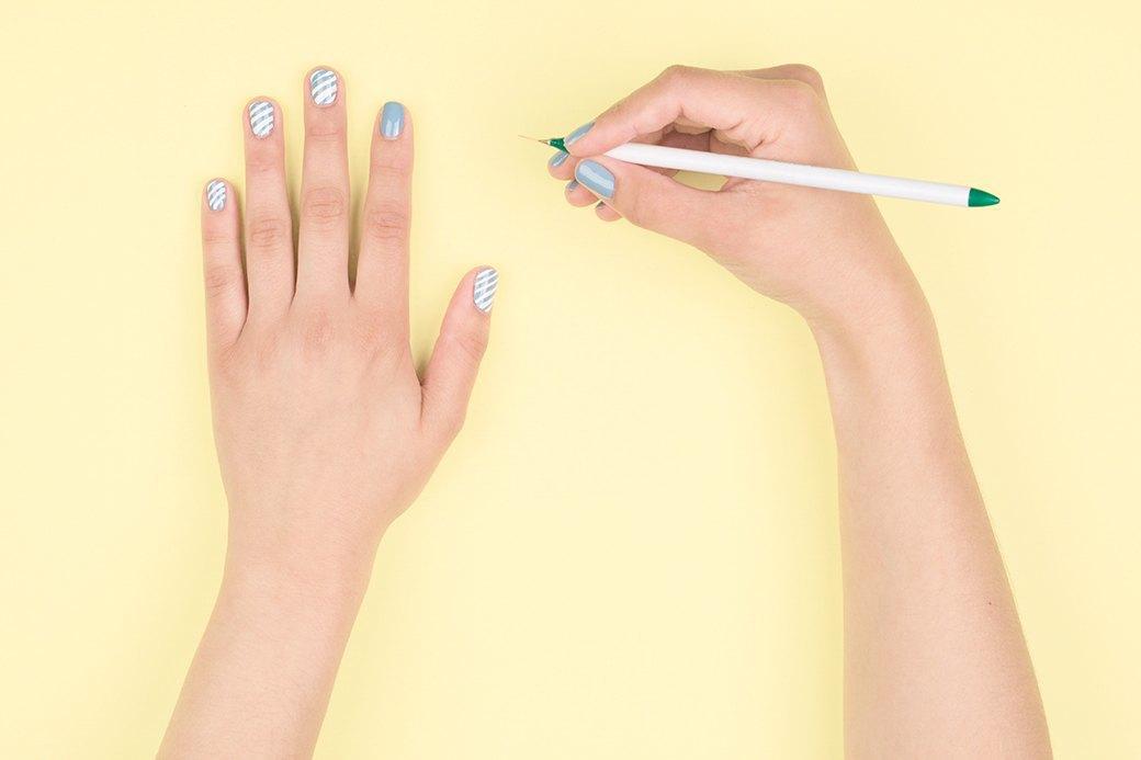 Тонкую кисть окунуть в плотный белый лак и начать рисовать тонкие линии наискось. Следите, чтобы на кисточку не набиралось слишком много лака, не то линии выйдут толстыми.. Изображение № 3.