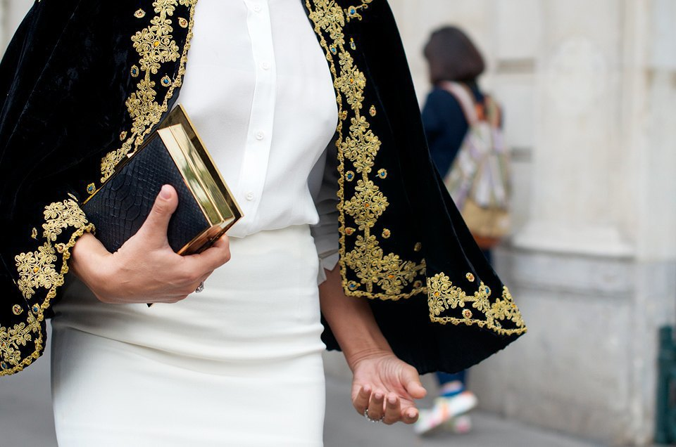 Золото и черный на кейпе и клатче гармонично перекликаются, а белые блузка и юбка создают удачный фон для них. Изображение № 27.