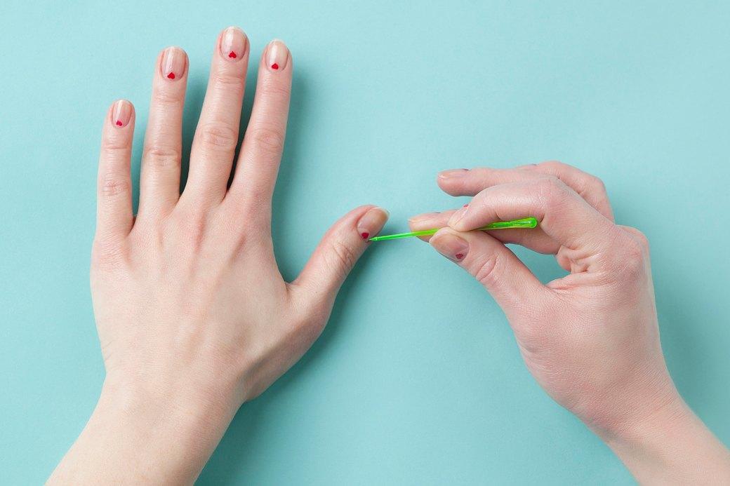 Поставить кистью у основания ногтя две красные точки рядом, соединить их в сердечко чистой зубочисткой. Вариант: окунать шпажку в пузырек лака, и проставлять точки ей. . Изображение № 3.
